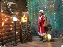 A Child In A Santa Claus Costume With A Bag In A Night Scene With Stars The Moon And Sparkling Lights