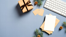 Cozy Winter Workspace Background. Flat Lay Gift Box, Keyboard, Blank Paper Card Mockup, Labels, Pine Branches With Cones On Blue Background. Top View Of Hygge Home Office Desk.