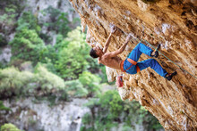 Rock Climber On Overhanging Cliff. Male Climber Gripping Small Handholds On Challenging Route.