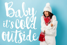 Young Woman In Winter Outfit Embracing Herself Near Baby Its Cold Outside Lettering On Blue