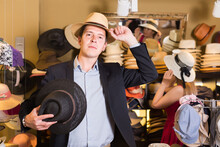 Portrait Of Smiling Russian Young Guy Try On Panama At Headwear Store