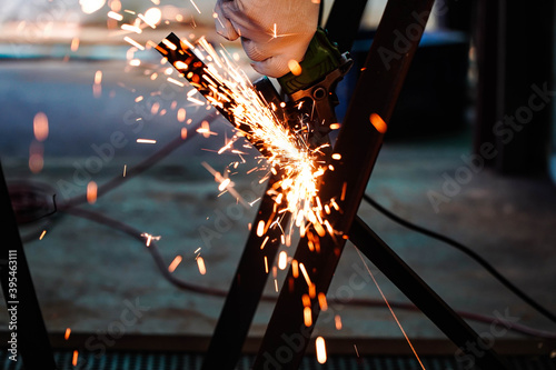 Fotografia Electric iron grinding machine in factory Sparks from grinding wheels
