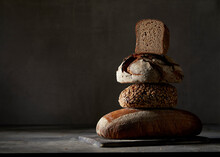 Four Different Breads, Stacked In Front Of A Dark Background