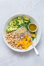 Vegetarian Salad With Avocado, White Beans, Arugula, Spinach, Sunflower Seeds, Orange And Quinoa