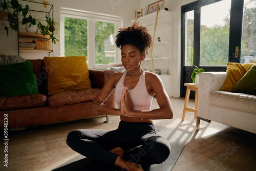 Fototapeta Young african woman sitting in lotus position with joined hands on yoga mat practicing breathing exercise obraz