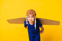 Happy Asian Handsome Funny Child Or Kid Little Boy Smile Wear Pilot Hat Playing And Goggles With Toy Cardboard Airplane Wings Flying, Studio Shot Isolated Yellow Background, Startup Freedom Concept