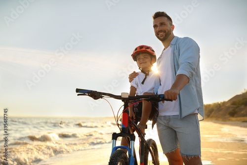 Fototapeta premium Happy father teaching son to ride bicycle on sandy beach near sea at sunset