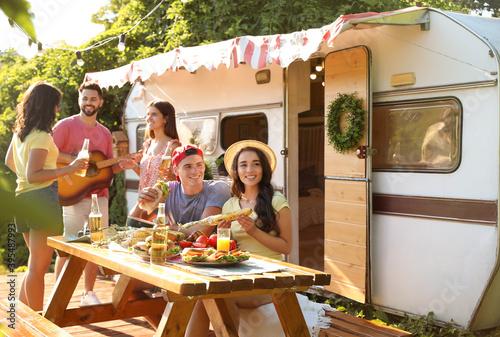 Slika na platnu Happy friends with drinks and food near trailer. Camping season