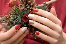 Female Hands With Christmas Nail Design. Red And Gold Nail Polish Manicure. Female Hands Hold New Year Decoration.