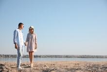 Happy Couple Walking Along Beach On Summer Day