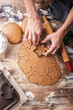 canvas print picture - Female hands preparing Christmas gingerbread cookie. Rustic table top background. Homemade delicious traditional pastries. Vertical shot