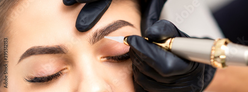 Obraz Beautician applying permanent makeup on eyebrows of young woman by special tattoo machine tool - fototapety do salonu
