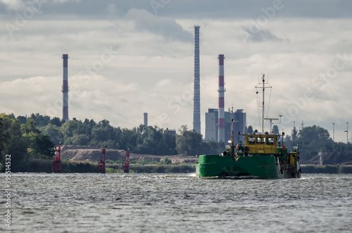 Fotografie, Obraz SCOW ON THE WATERWAY - A barge on the background of the coast with industrial ch
