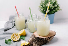 Taste Lemonades In Stylish Tumblers With Colorful Plastic Tubes Serving On Wooden Slice