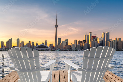 Fototapeta premium Toronto skyline in wooden pier with white chairs at sunset in Toronto, Ontario, Canada.