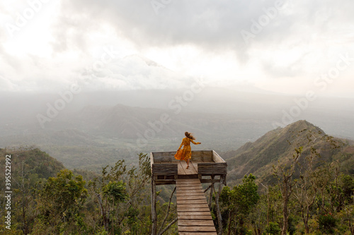 Vászonkép Travel blogger woman stands on viewpoint in the muntains,  Bali landmark volcan