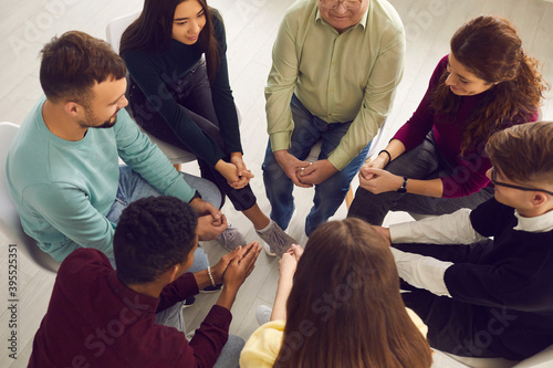 Foto Diverse people sitting in circle and sharing their stories in group therapy sess