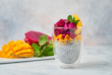 Chia Pudding Decorated With Slices Of Mango Red Pitaya And Fresh Mint In Glass