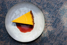 A Slice Of Mango Tart With Yoghurt Cream, A Biscuit Base And Berry Sauce