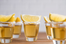 Glass Sots With Golden Tequila And Slices Of Lemon On Wooden Table