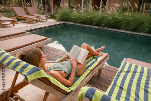 Canvas Woman reading a book  and relaxing near  swimming pool, lie on deck chair with s