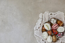Colorful Easter Eggs In A Basket With Lace Doilies