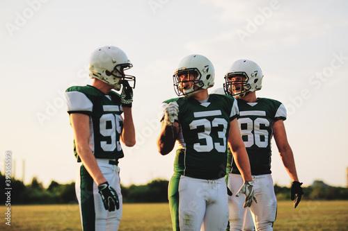 Slika na platnu Young American football players walking off a field after practi