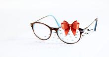 Occhiali Da Vista E Fiocco In Nastro Rosso Isolato Su Sfondo Bianco. Carta Regalo Occhiali Da Vista Di Natale.