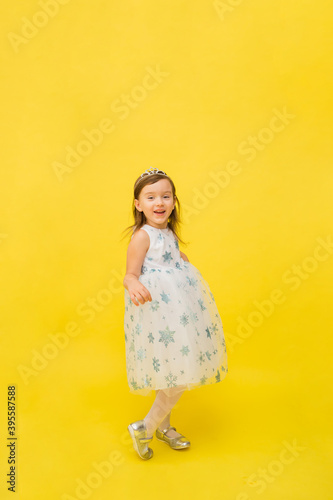 Fotografia little girl in a puffy white dress with snowflakes on a yellow background with s