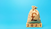 British Pound Sterling Money Bag And Blocks 2021. Budget Planning For Next Year. Beginning Of New Decade. Business Plans And Development Prospects. Revenues Expenses, Investment And Financing.