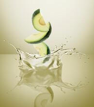Avocado Wedges Splashing Into Oil