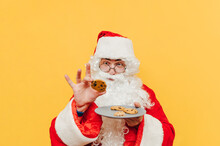 Portrait Of Funny Santa Claus Holding A Plate With Cookies, Taking One Biscuit In His Hand, Looking At The Cookie, Feeling Excited And Curious.