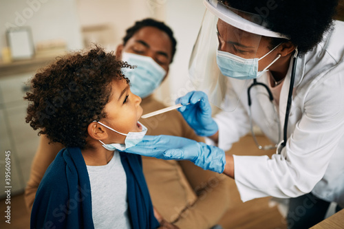 Fototapeta African American doctor with face mask examining boy's throat during a home visit. obraz