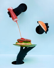 Hand In Black Gloves Holding Plate With Burger And Spilling Ketchup On Patty Against Blue Background