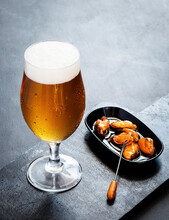 Fresh Beer Served With Marinated Mussels On Dark Background