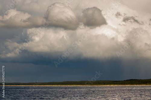 Fototapeta Krajobraz nad wodą na tle  zachmurzonego nieba z lasem na horyzoncie obraz