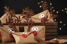 Gifts In Envelopes With Deer Faces On Wooden Table Against Blurred Lights. Christmas Advent Calendar