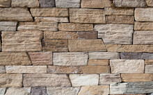 The Texture Of The Wall Is Made Of Stone Blocks Of Brick.Earthen Colors Of A Brick Wall Of Various Shapes.Background, Wallpaper, Seamless.