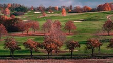 A Golf Course Not Far From Prague, Czechia. Trees Colored In Autumn Shades Frame The Golf Field. Golfers Moving On The Field, Golf Carts Riding Nearby. It Is A Beautiful Sunny Day With Clear Skies.