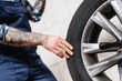 Leinwandbild Motiv partial of tattooed technician touching car wheel in workshop on blurred background