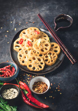 Lotus Root Or Rhizome Stir-fry With Spices, Different Types Of Hot Peppers, Soy Sauce And Sesame Seeds On A Dark Rustic Stone. Asia Dinner Concept