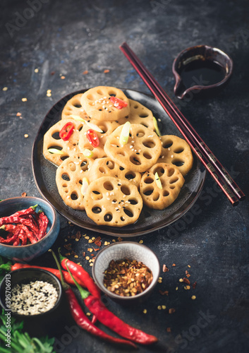 Fotografie, Obraz Lotus root or Rhizome stir-fry with spices, different types of hot peppers, soy sauce and sesame seeds on a dark rustic stone