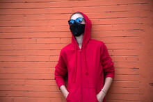 Caucasian Girl In Red Sport Hoodie With Hood Put On Head In Black Sunglasses And Black Protective Medical Mask. Winter Style In Covid World. Protection For Travellers. Orange Brick Wall Behind. Youth