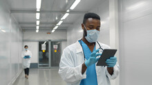 African Doctor Wearing Protective Mask And Gloves Using Tablet Working In Clinic