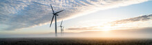 Three Commercial Wind Turbines In Thick Fog At Sunrise In The English Countryside Panoramic