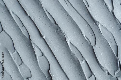 Fototapeta Gray bentonite facial clay (alginate mask, face cream, body wrap) texture close up, selective focus. Abstract background with brush strokes. obraz