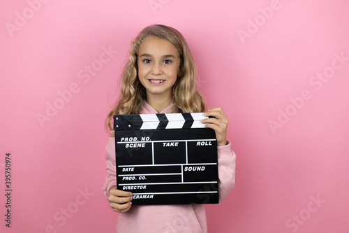 Photo Young beautiful child girl standing over isolated pink background holding clappe