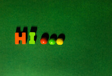 Colorful Wooden Letters Text Word Hi Inscription With Ellipsis Beads At Green Craft Paper Background, Friendly Greeting