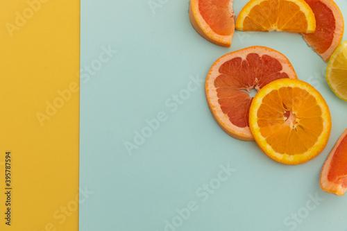 Slices of grapefruit, orange and lemon on blue and yellow background