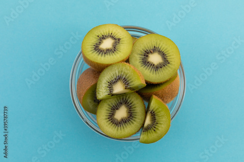 High angle view of bowl of freshly cut kiwi on blue background
